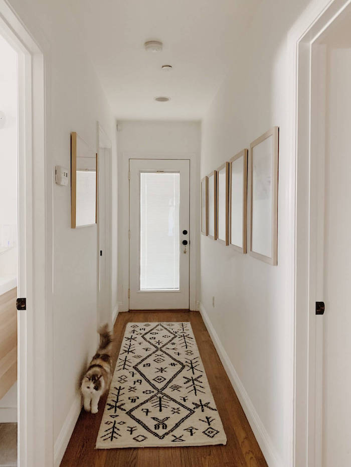 white and black rug on wooden floor entry way decorating ideas framed art hanging on white walls