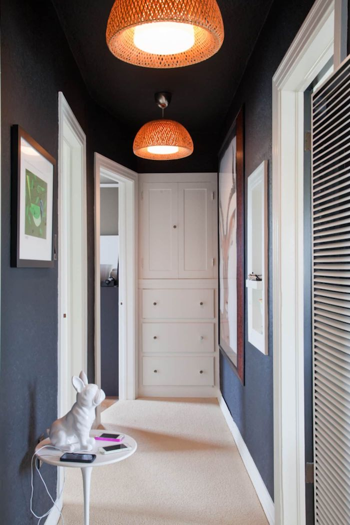 white doors and cupboard decorating ideas for stairs and hallways framed art hanging on dark blue walls