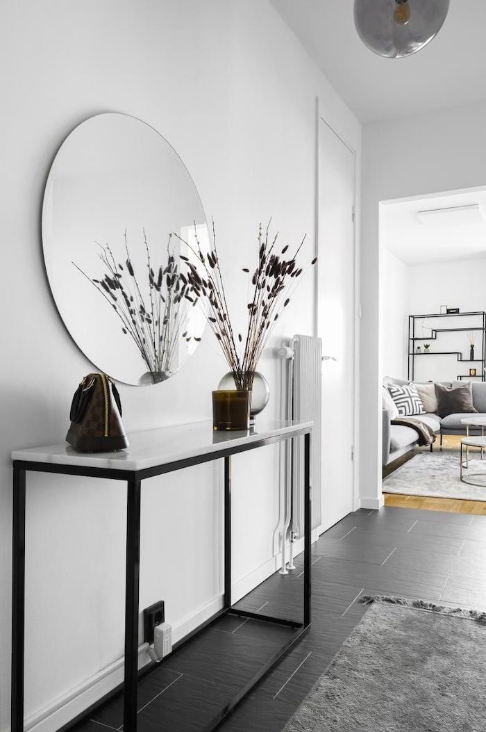 white walls large round mirror hanging above table entryway design ideas black tiles on the floor gray rug