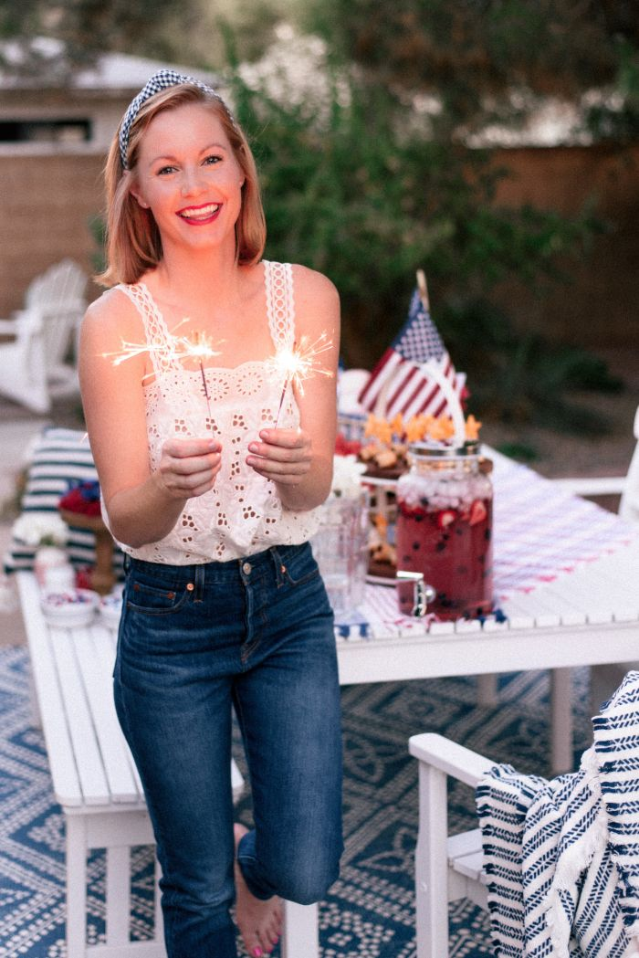 woman standing next to table decorated with american flags 4th of july outfits wearing jeans white lace top