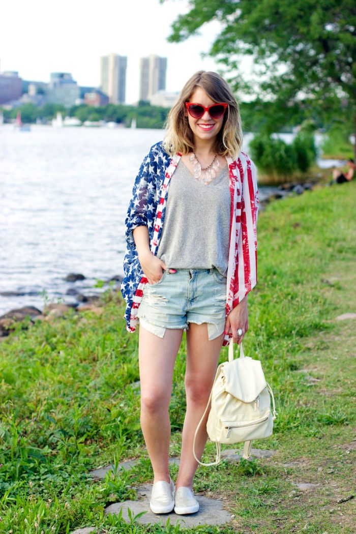 woman wearing denim shorts gray t shirt american flag jacket 4th of july shirts for women carrying white backpack