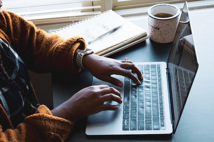 woman wearing orange sweater typing on laptop keyboard working from home coffee mug next to her