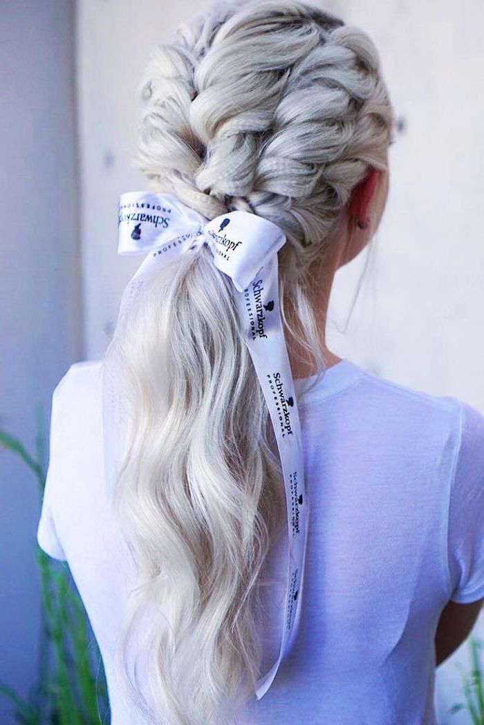 woman with long blonde hair short crimped hair four braids tied in low ponytail with white bow