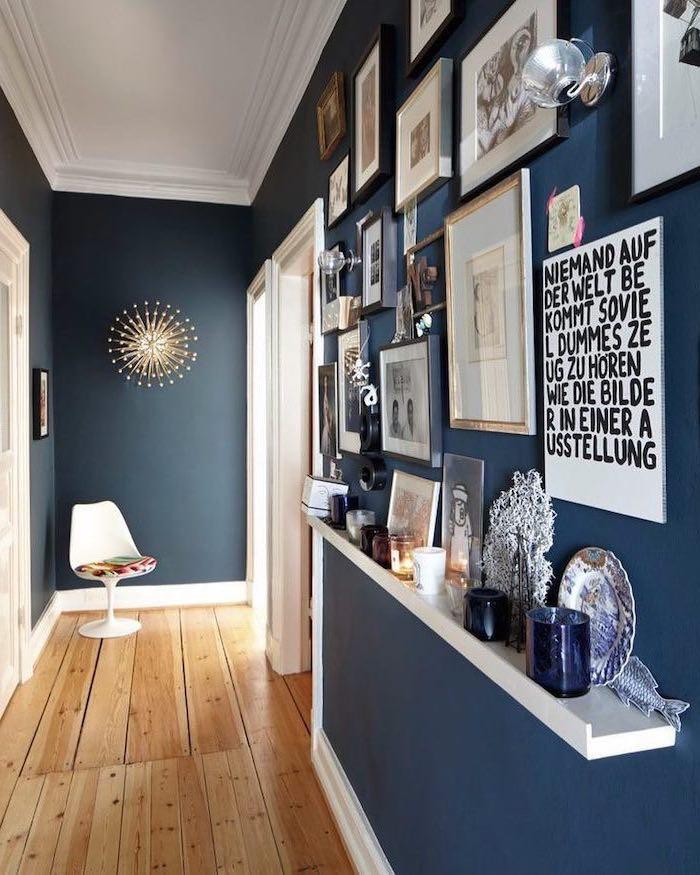 wooden floor dark blue walls narrow hallway ideas lots of framed art hanging on wall and on floating shelf
