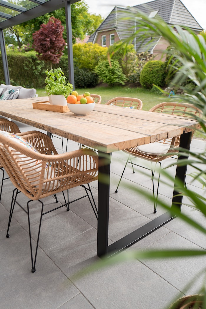 wooden table and chairs on concrete tiles farmhouse garden table bowl full of fruits on top