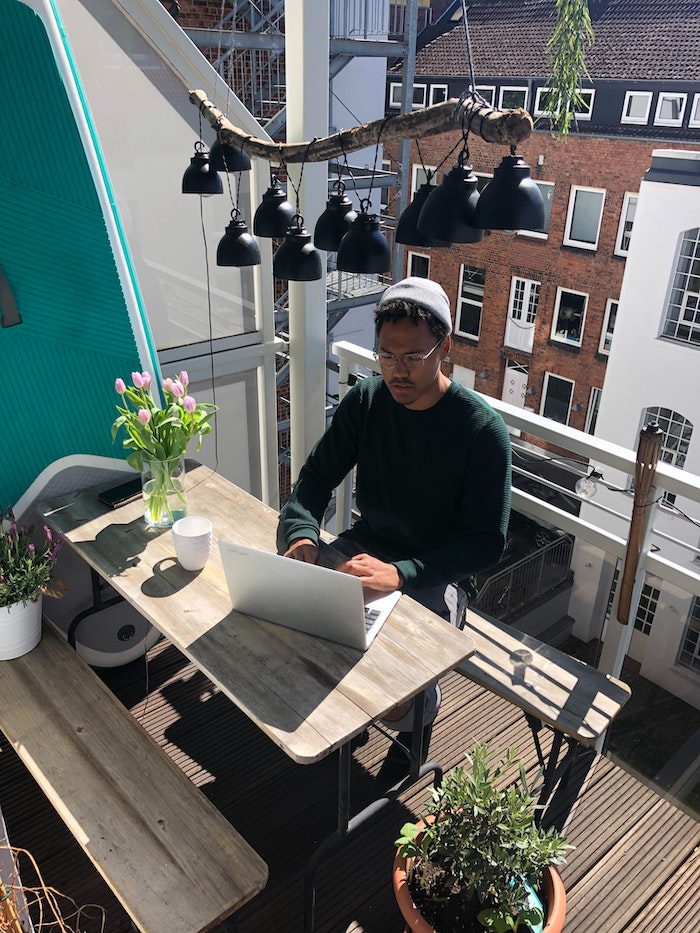 working from home man sitting on his balcony laptop opened on wooden table