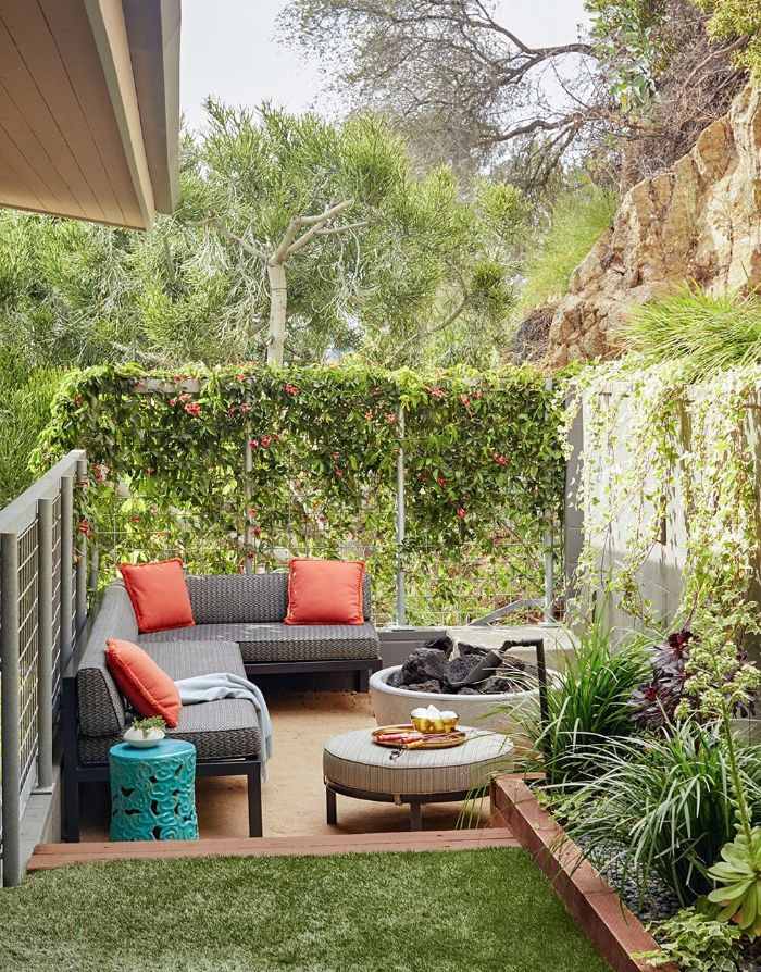 backyard décor ideas small wooden corner sofa with orange throw pillows ottoman next to fire pit