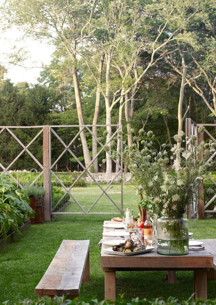 backyard design ideas wooden bench and table in the grass surrounded by plants and trees