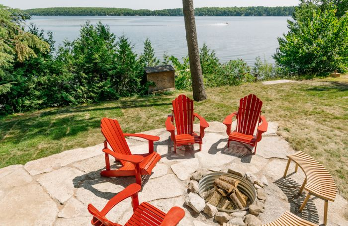 backyard patio ideas on a budget four red wooden lounge chairs wooden benches arranged around fire pit