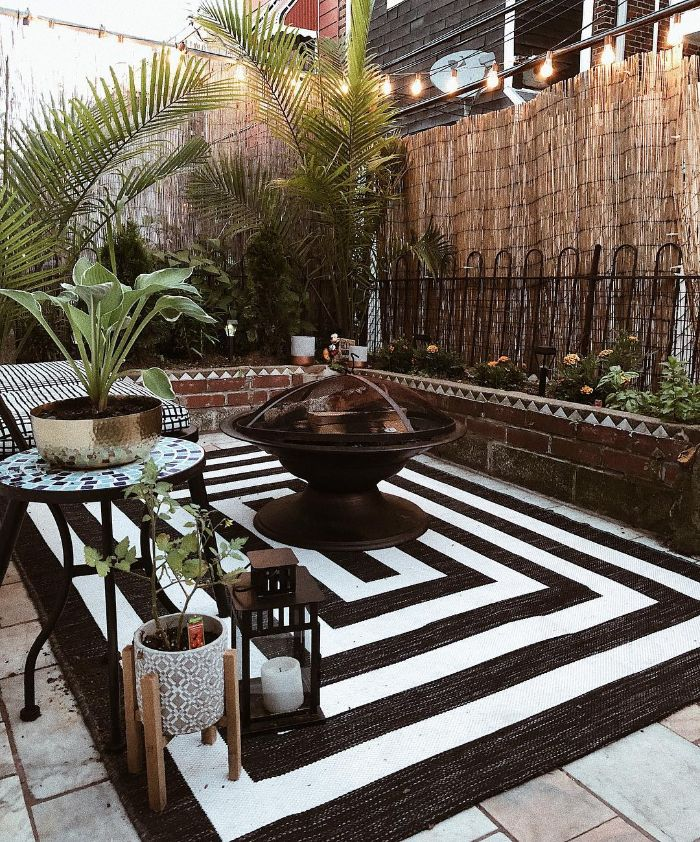 black and white rug under fire pit black metal bench table next to it backyard ideas on a budget lanterns