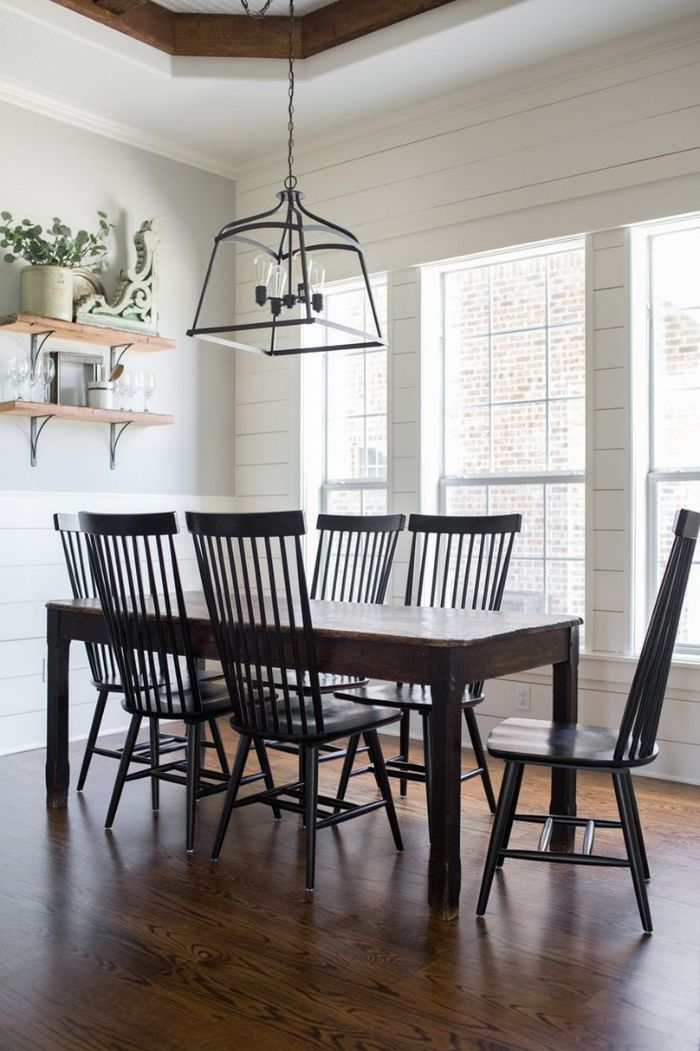 black chairs around vintage table in front of tall windows farmhouse dining room open shelving