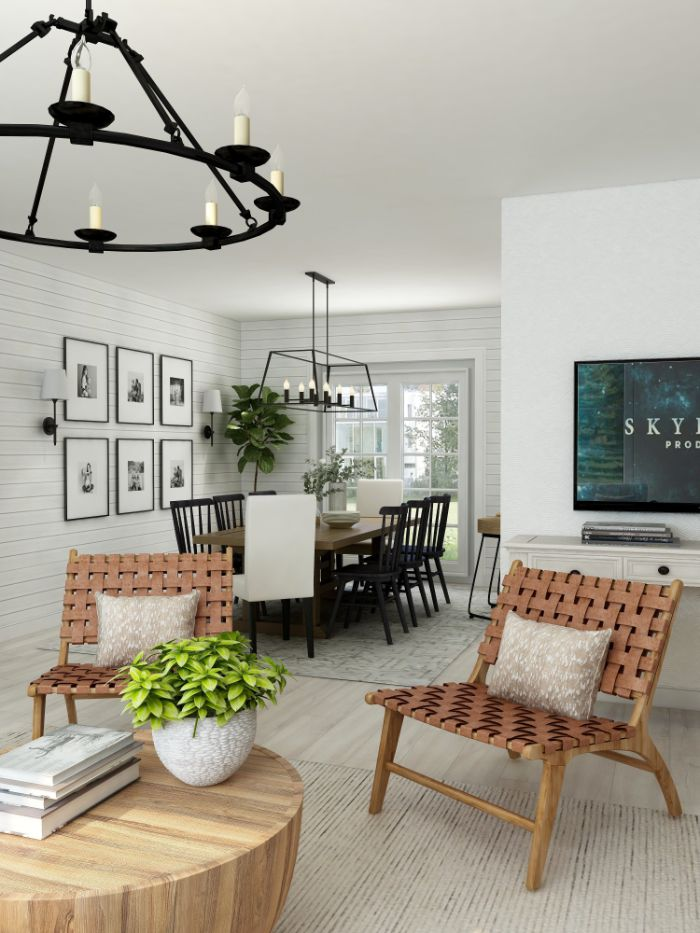black chandeliers hanging above farmhouse table and chairs in black and white shiplap on the walls