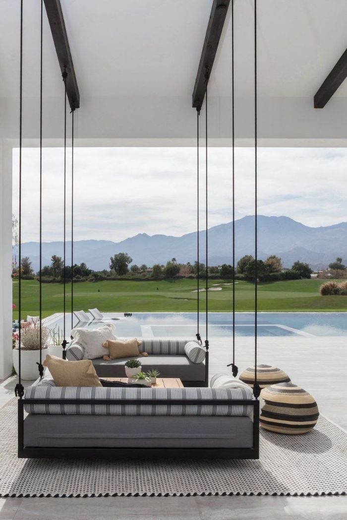 black swings with gray cushioning hanging from the ceiling backyard design ideas next to the pool