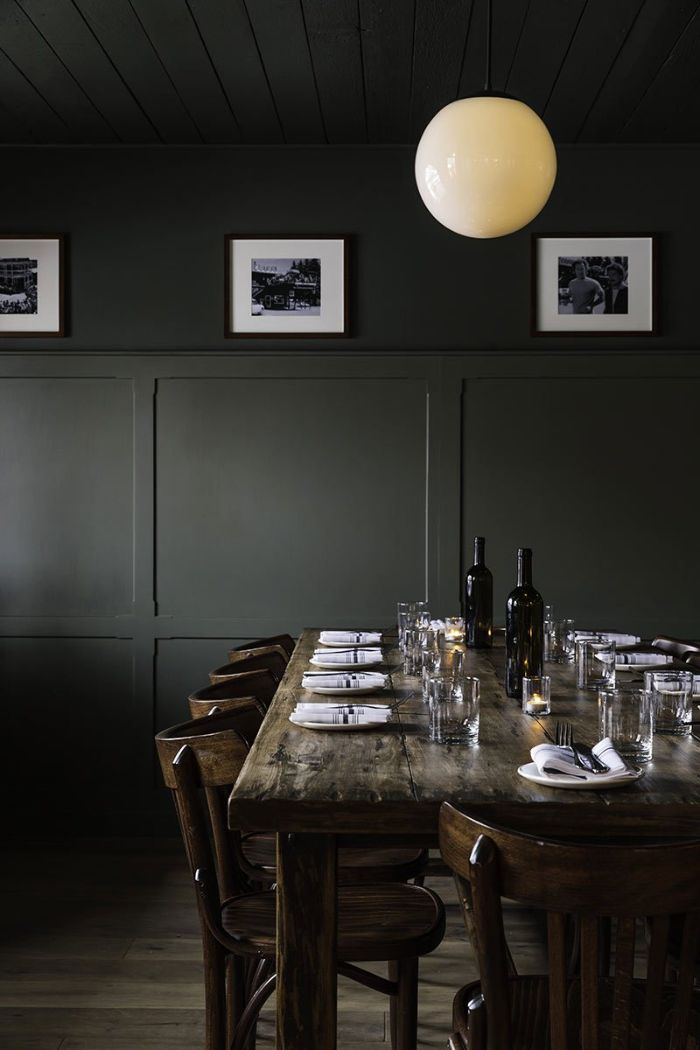 black walls with black and white photographs dining room table decor vintage salvaged wood table and chairs