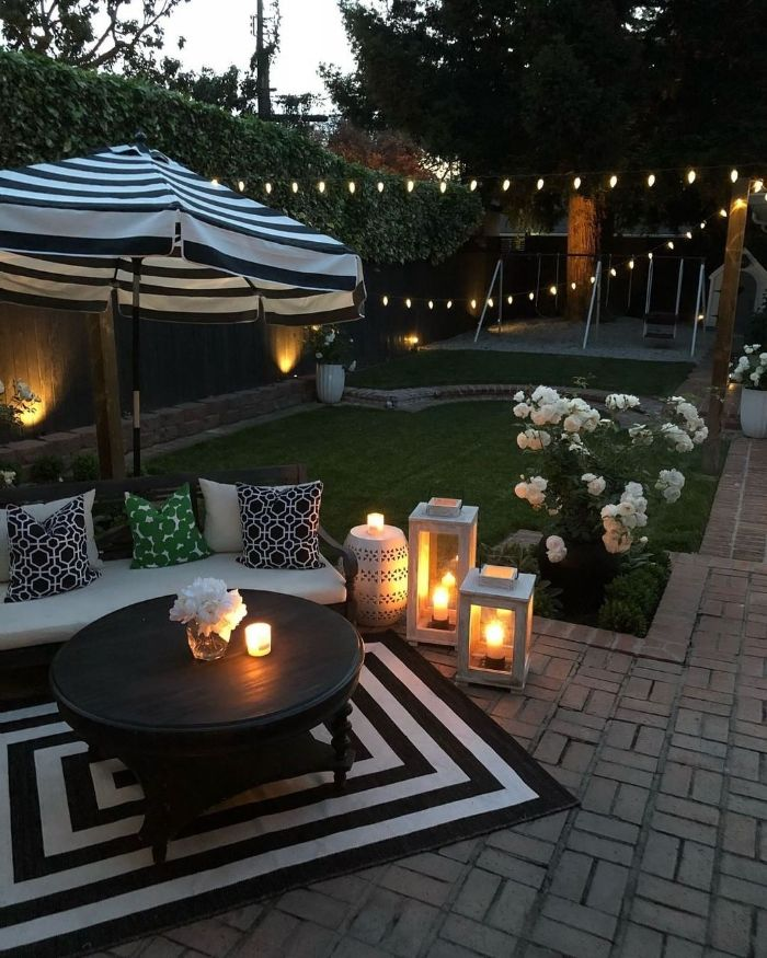 black wooden table with wooden bench next to it black and white rug and umbrella backyard ideas on a budget lanterns