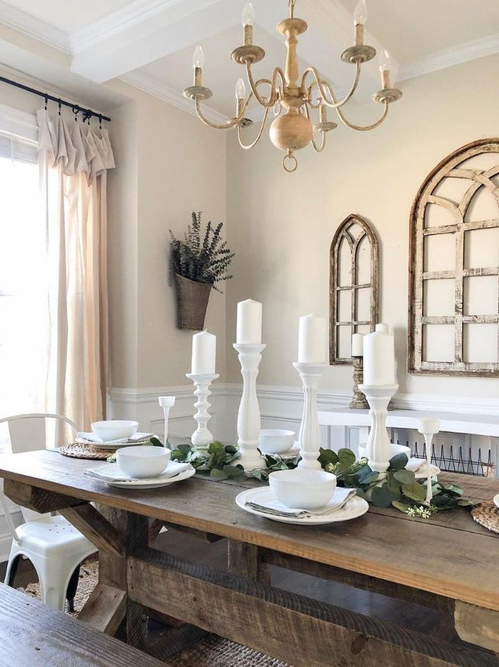brass chandelier hanging above salvaged wood table with bench next to it rustic dining table candlesticks on it