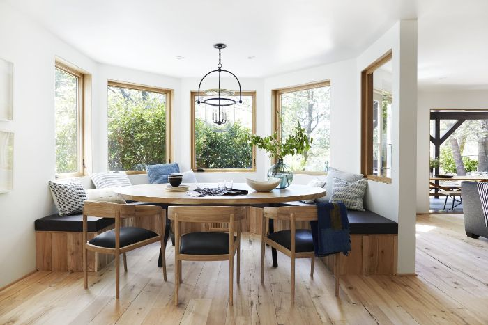 breakfast nook with round rustic dining table bench and chairs around it blue and white throw pillows