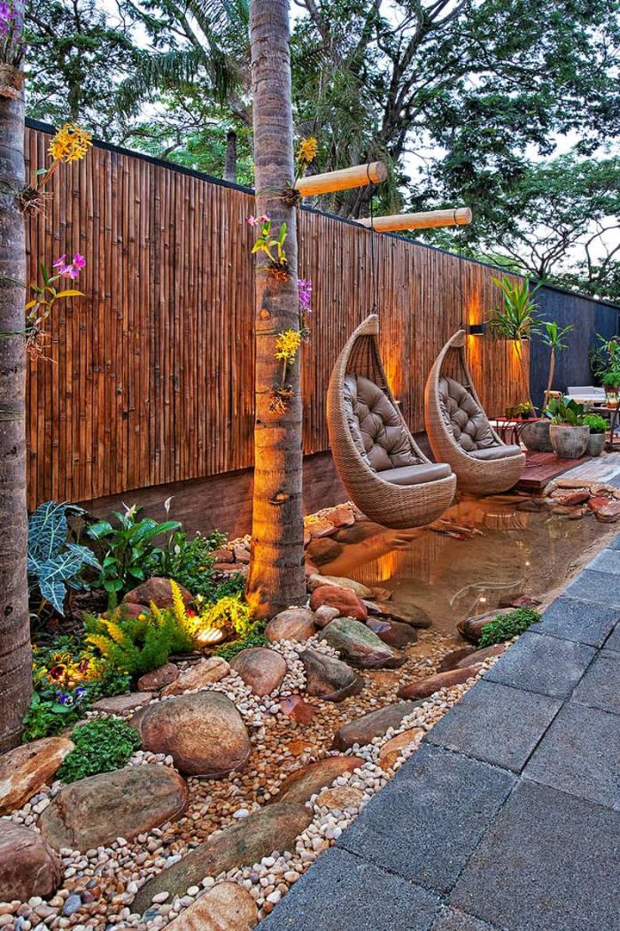 brown leather cushions on two swings over small pond landscape design ideas surrounded by rocks and plants