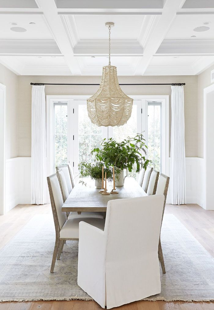 chandelier hanging above long rustic dining table white wooden chairs around it tall windows