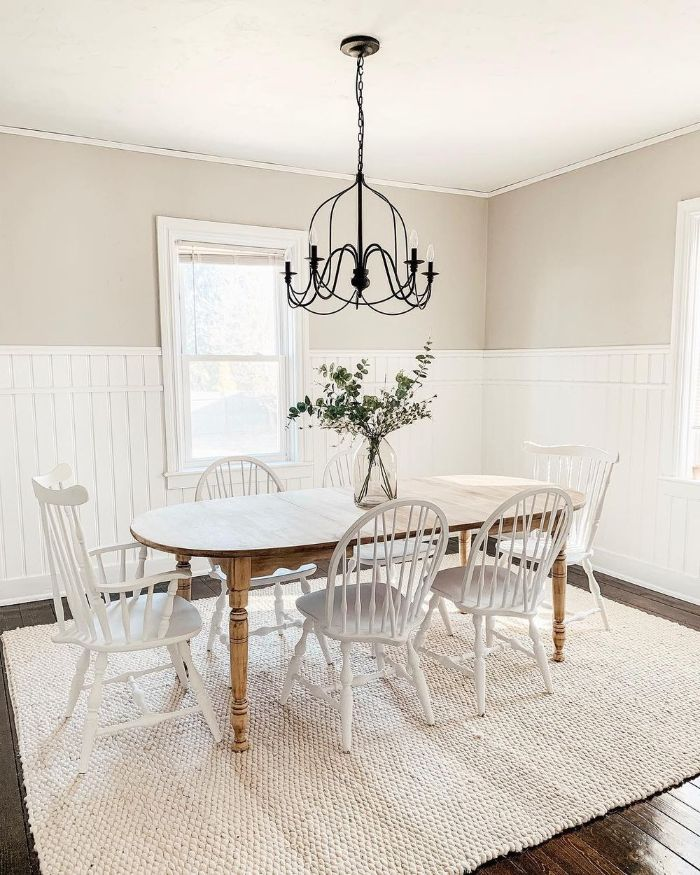 chandelier hanging above table with white wooden chairs around it dining room table decor shiplap on the walls
