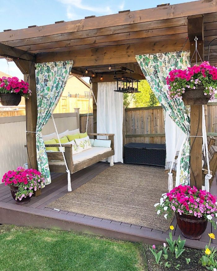 colorful curtains hanging from wooden pergola backyard design ideas wooden swing underneath