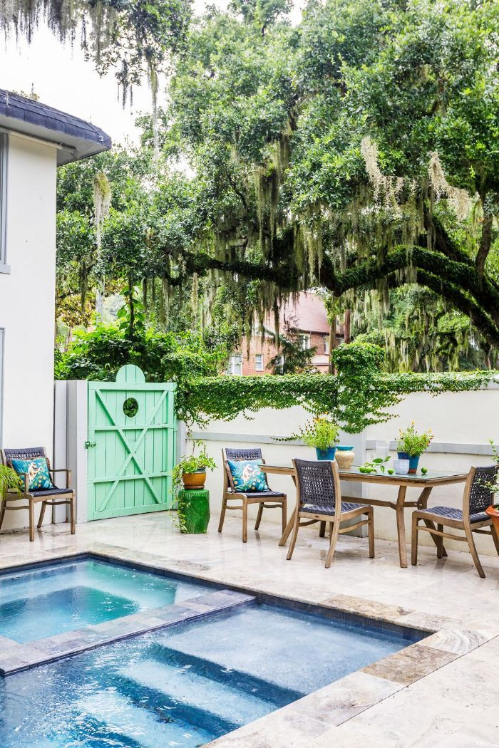 dining area next to the pool table and wooden chairs backyard patio ideas under large tree