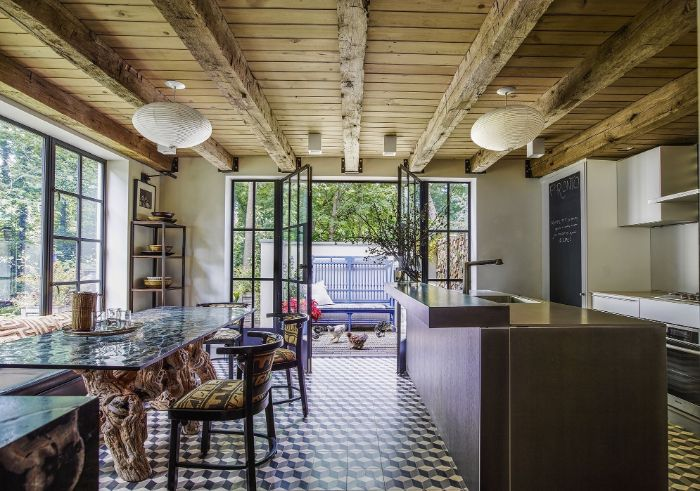 exposed wood beams colorful tiles on the floor modern farmhouse dining room kitcchen island and furniture with colorful textiles