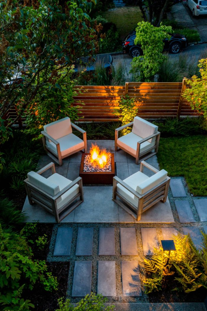 fire pit with four lounge chairs around it with white cushions landscape design ideas tiled pathway