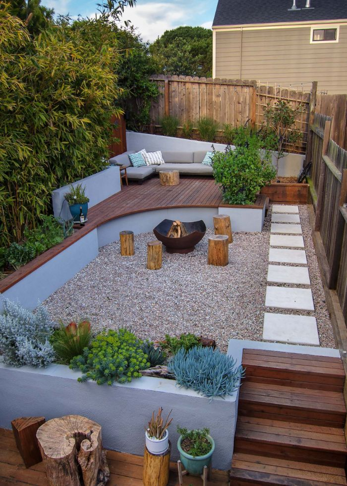fire pit with four wooden logs around it backyard patio ideas lounge area with gray sofa