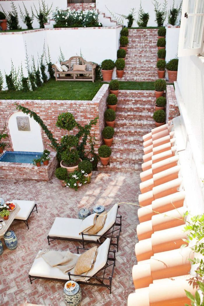 fountain next to lounge area small backyard patio ideas terraced backyard with stairs and lots of plants