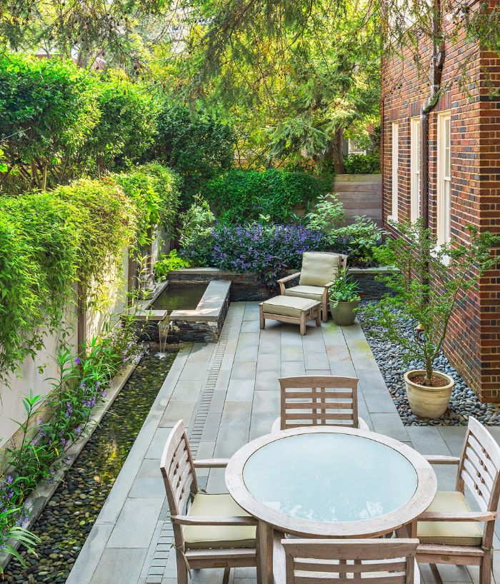 fountain with lounge chair next to it dining area backyard décor ideas surrounded by flowers and trees