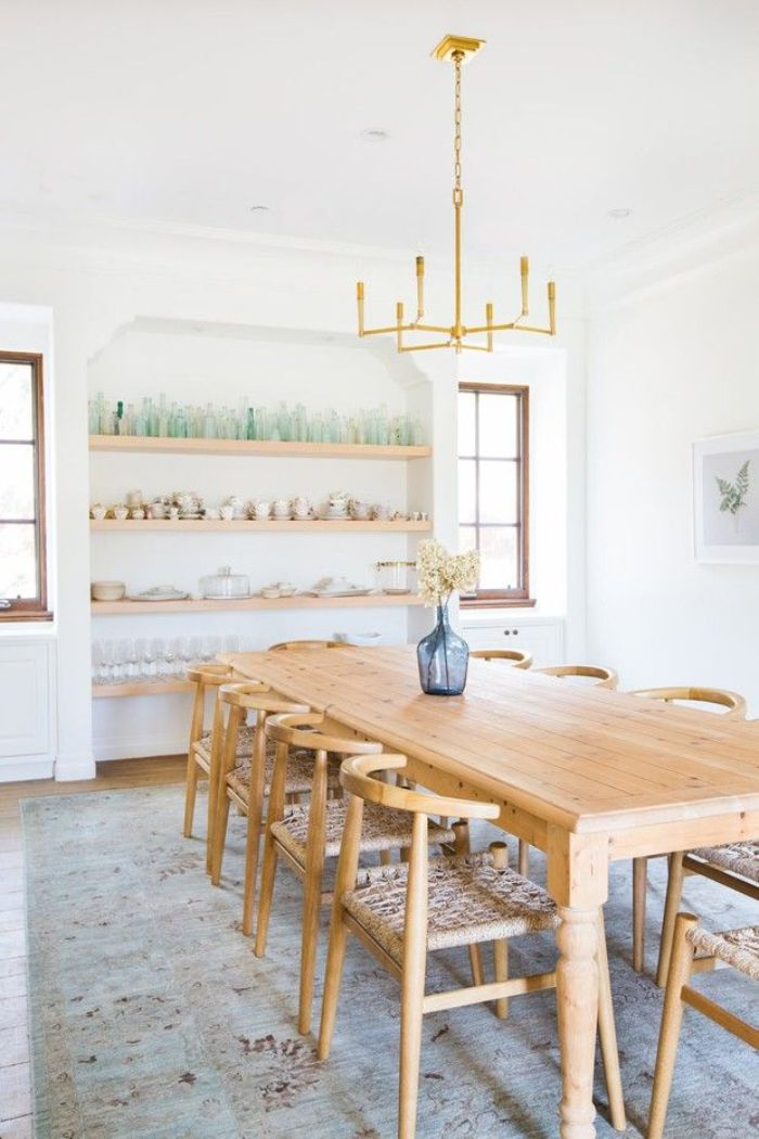 glasses and cups arranged on open shelves on the wall rustic dining table with wooden chairs