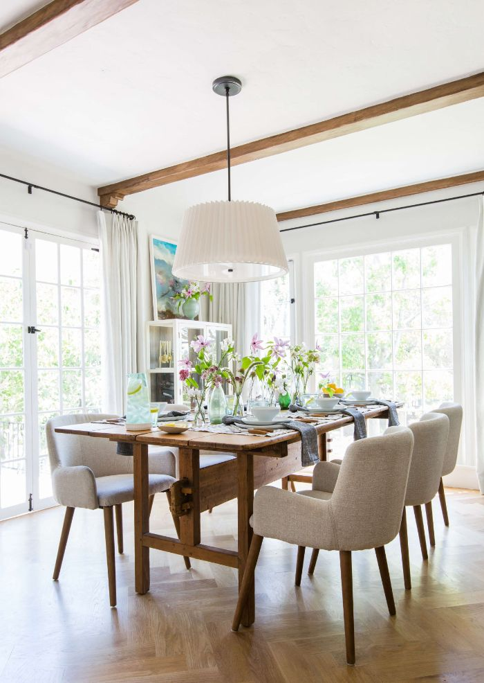 gray chairs around long wooden table farmhouse dining table exposed wood beams on the ceiling