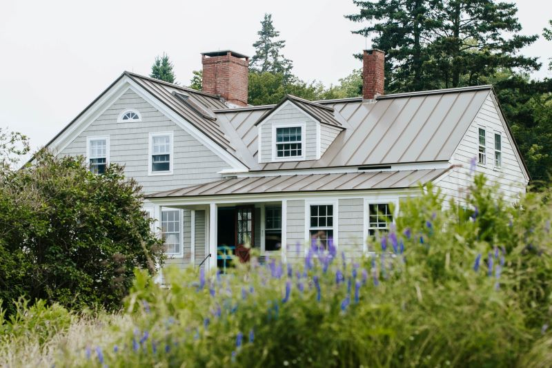 gray house remodeling expenses surrounded by bushes trees