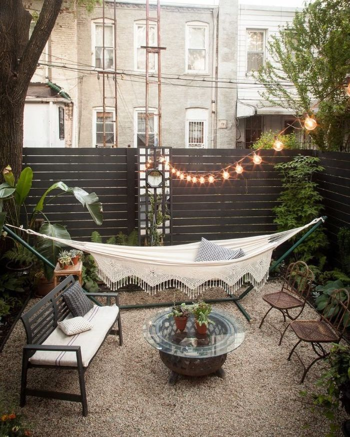 hammock wooden bench table and chairs placed on gravel diy backyard ideas fairy lights above them