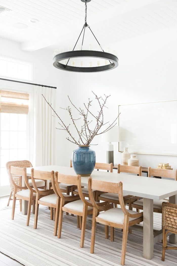 large vase placed on long table with wooden chairs farmhouse dining table hanging chandelier