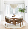 large windows with white curtains farmhouse dining room round wooden table and chairs with gray cushions