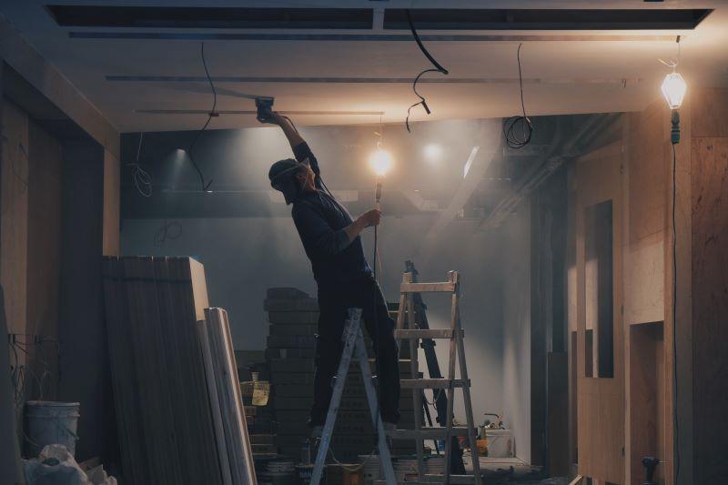man on ladder remodeling expenses dark room