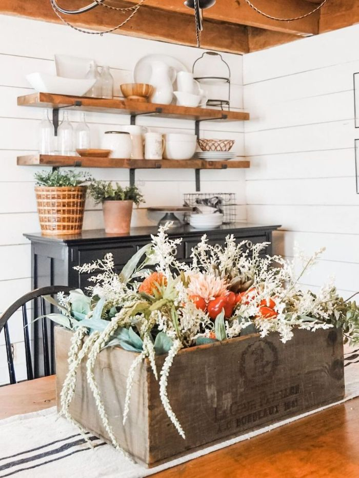 open shelving above black cupboard farmhouse table and chairs wooden crate with flowers on the table