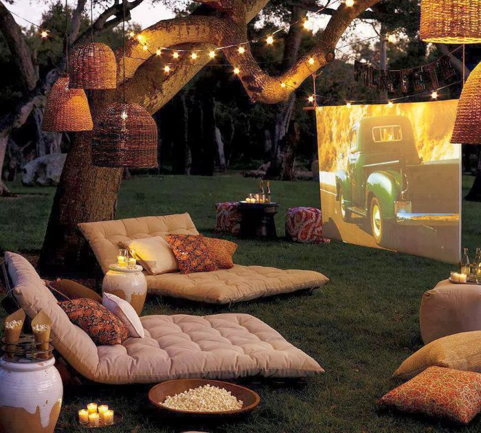 outside theater white cushions on the grass white screen lanterns fairy lights hanging from tree backyard ideas on a budget