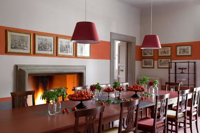 red wooden table and chairs modern farmhouse dining room next to fireplace art hanging on the wall