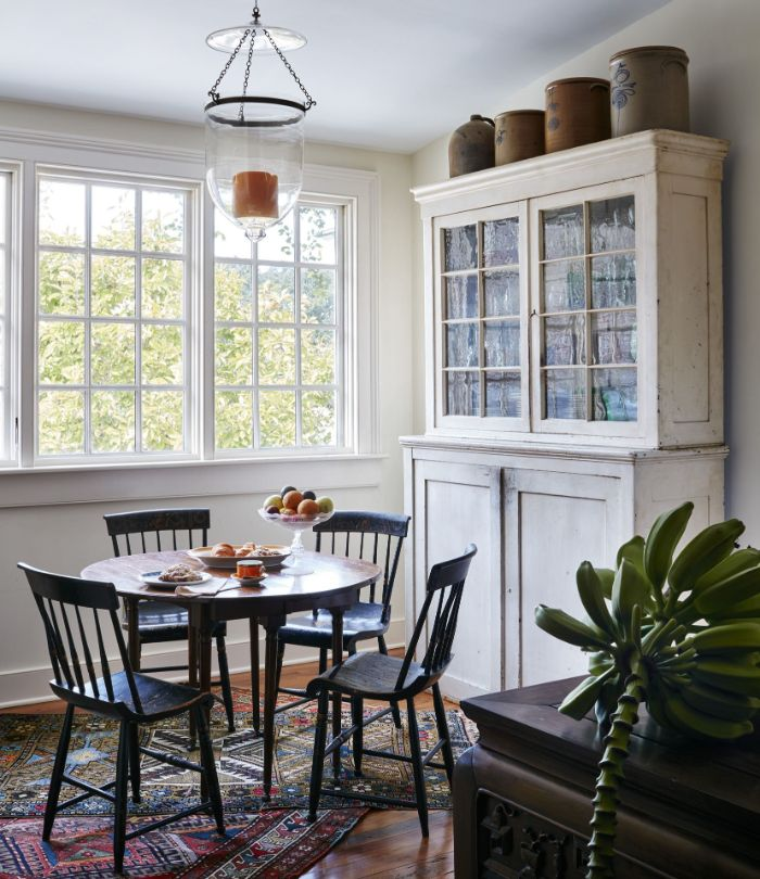 round table with vintage chairs and cupboard next to it dining room table decor ideas mismatched rugs