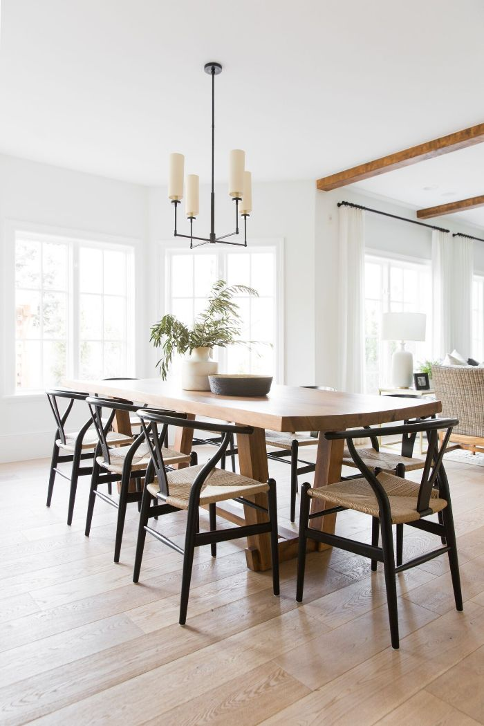 rustic dining table made of wood black chairs around it minimalistic design