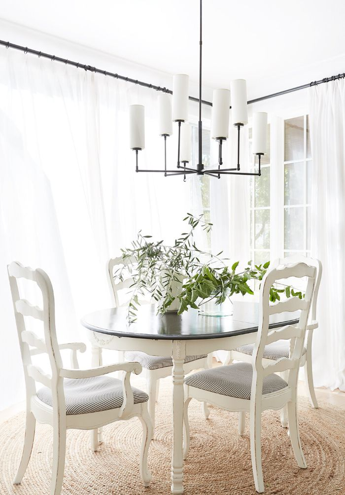 salvaged wood chairs and farmhouse kitchen table chandelier hanging above it