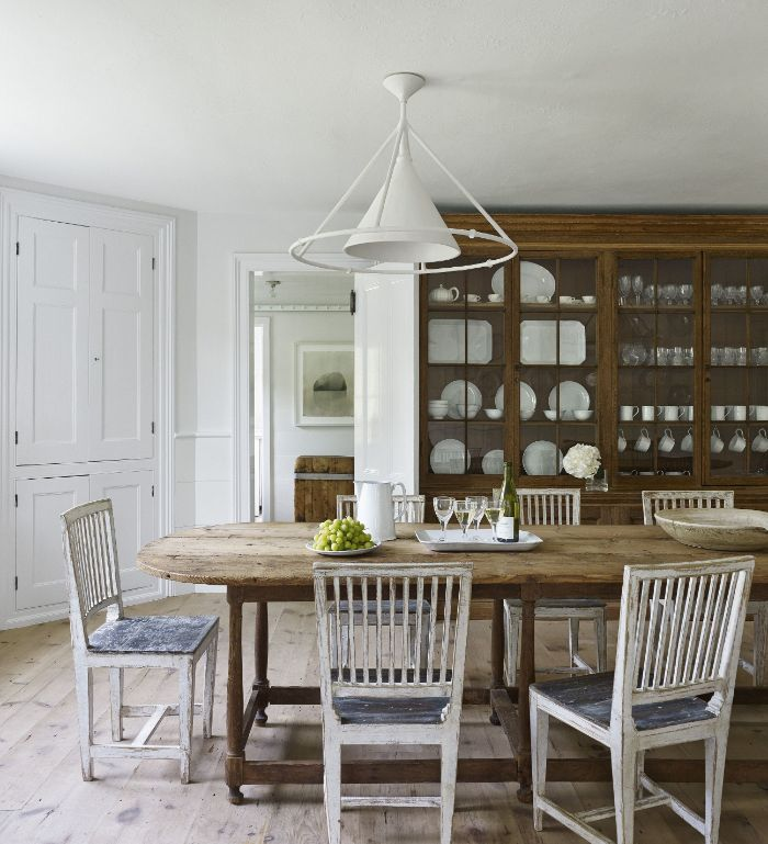 salvaged wood farmhouse table and chairs cupboard with dinner plates and glasses arranged inside