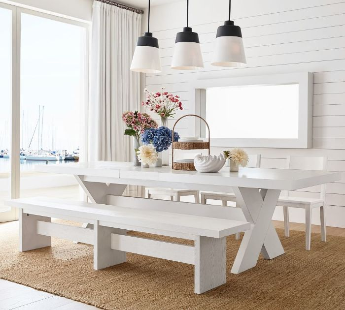 shiplap on the wall tall window modern farmhouse dining room white wooden table with bench and three chairs around it