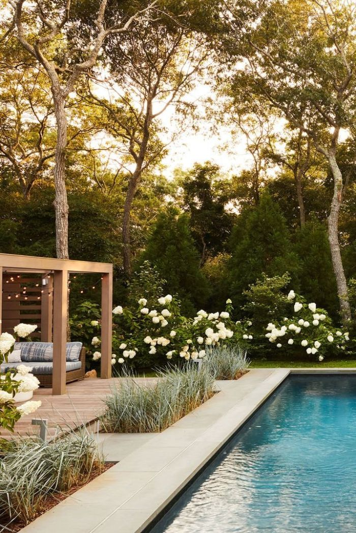 small backyard patio ideas large pool pergola with lounge area fairy lights surrounded by lots of trees white flowers