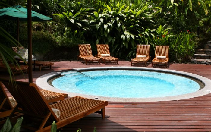 small round pool surrounded by wooden lounge chairs small backyard patio ideas lots of plants and trees
