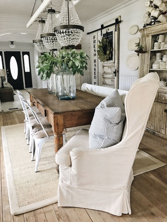 white armchair vintage chairs and table three chandeliers above it barn doors farmhouse kitchen table