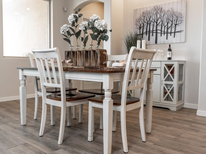 white chairs around table next to white cupboard modern farmhouse dining room flower bouquet on the table